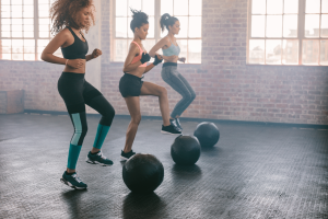 Three women in a HIIT workout class