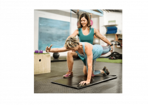 Female person trainer doing core stabilisation exercises with a female client