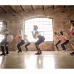A group of ladies in a group exercise session with a female trainer